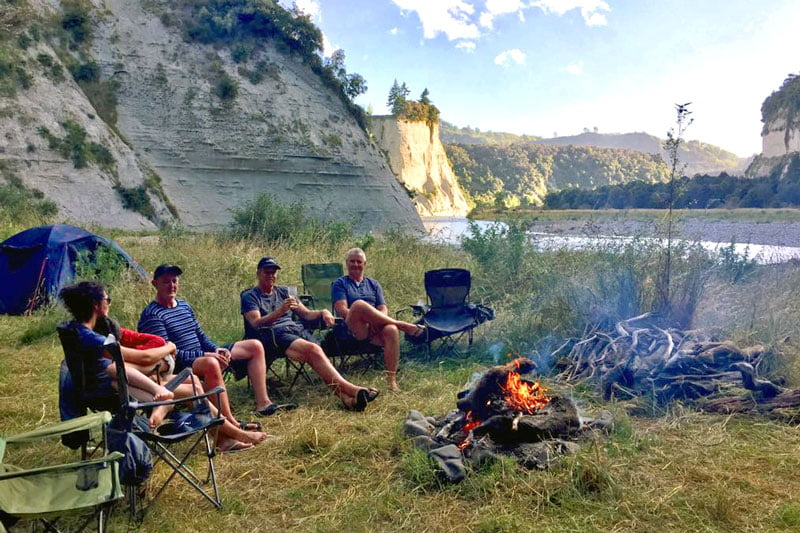 Four people sitting on camp chairs next to a bonfire near the river